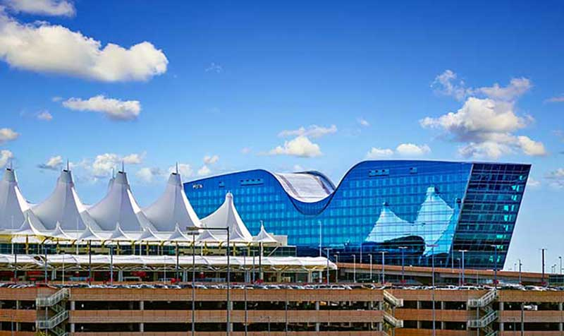 Denver International Airport with sky and clouds reflection. Photo courtesy of Flickr