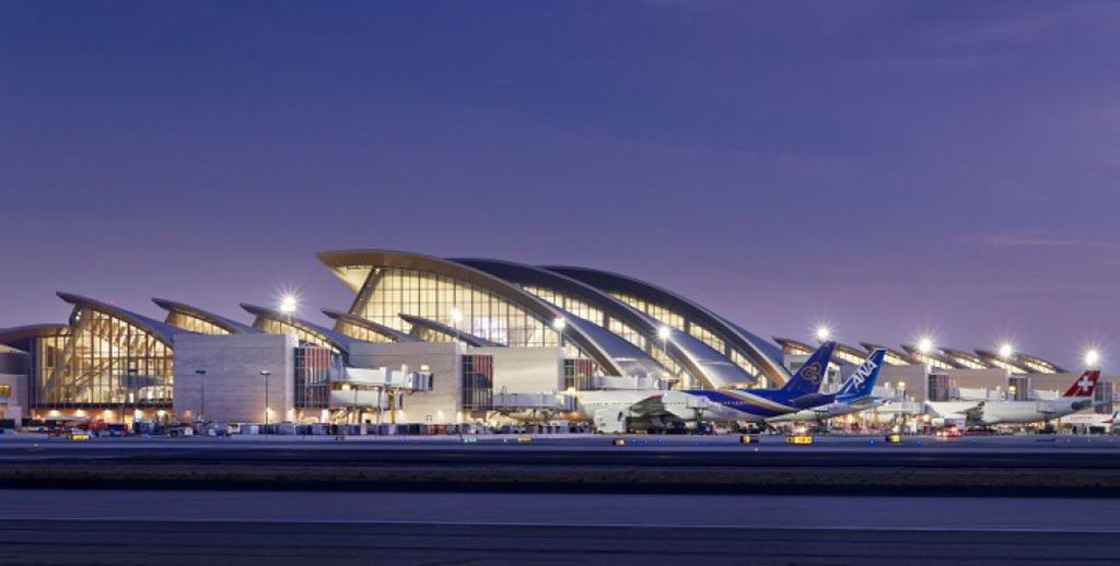 LAX terminal and planes at sunset with lights of the terminal showing brightly. Photo courtesy of AECOM.