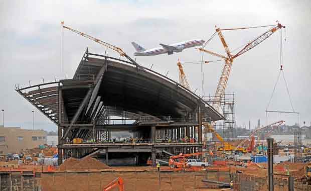 Terminal under construction with plane flying behind. Photo courtesy of Scott Varley/Daily Breeze